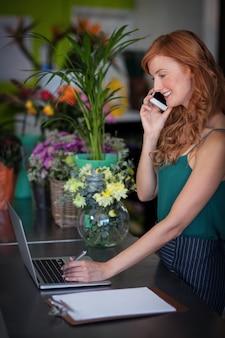 Fleuriste femme parlant sur téléphone mobile tout en utilisant un ordinateur portable