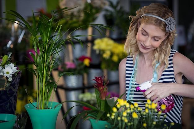 Fleuriste femme pulvérisant de l'eau sur les fleurs