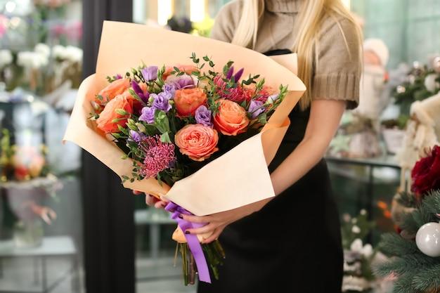 Fleuriste femme tenant beau bouquet dans un magasin de fleurs