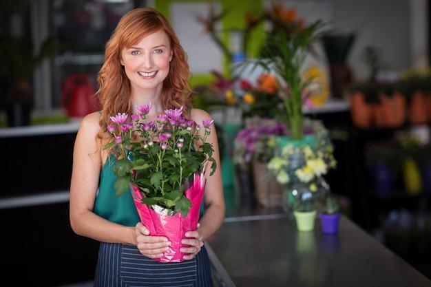Fleuriste femme tenant un bouquet de fleurs dans un magasin de fleurs
