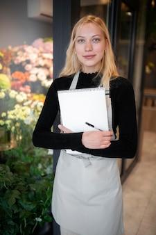 Fleuriste femme tenant un cahier