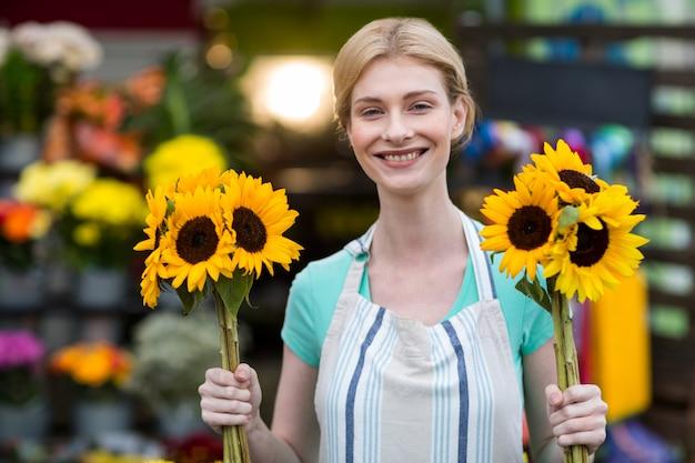 Fleuriste femme tenant des fleurs dans un magasin de fleurs