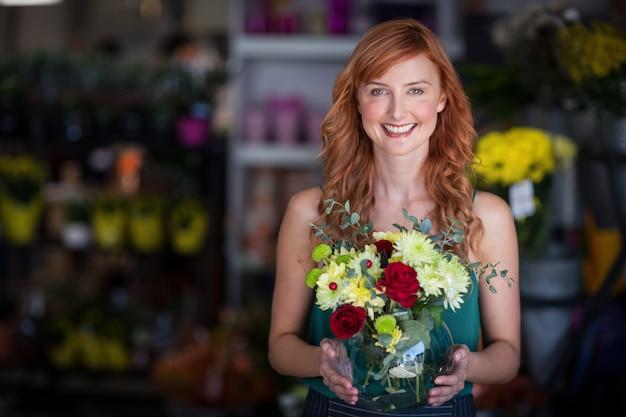 Fleuriste femme tenant un vase à fleurs au magasin de fleurs