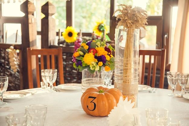 Fleuriste festive de style automne avec numérotation des tables sur les citrouilles dans la salle de banquet. fleuristerie et décoration d'arrangements floraux événementiels.