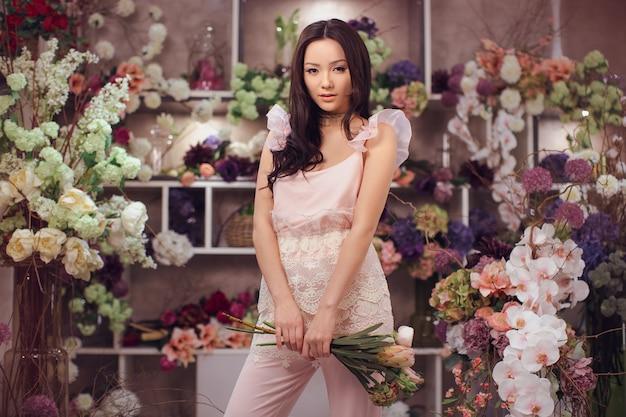 Fleuriste. fille et bouquet de fleurs de pivoines dans les mains. femme debout contre bokeh floral