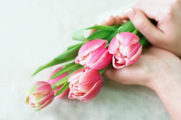 Fleuriste en gros plan avec des fleurs. fleuriste tenant un bouquet de tulipes roses. concept de magasin de fleurs.