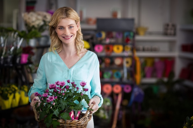 Fleuriste heureux holding panier de fleurs