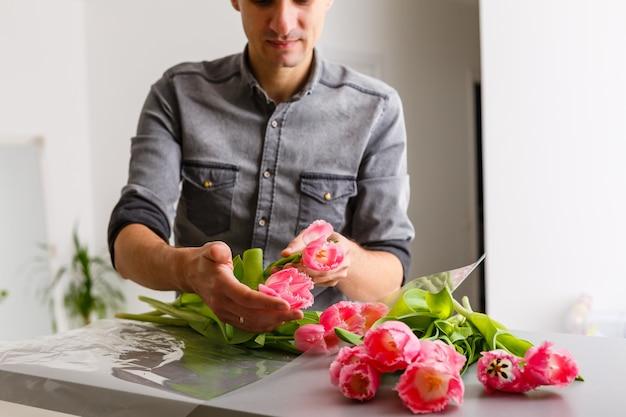 Le fleuriste de l'homme fait un bouquet de tulipes rouges et l'emballage en pack sur une table en bois. fleurs