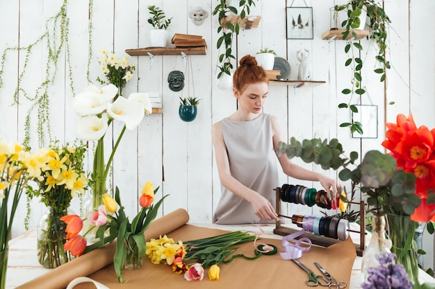 Fleuriste de jeune femme faisant le bouquet de fleurs et de rubans