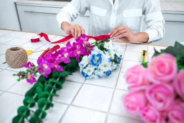 Fleuriste jeune femme faisant des fleurs artificielles bricolage