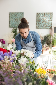 Fleuriste mâle regardant une belle fleur blanche dans la boutique