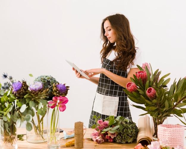 Fleuriste moyen avec tablette et tablier