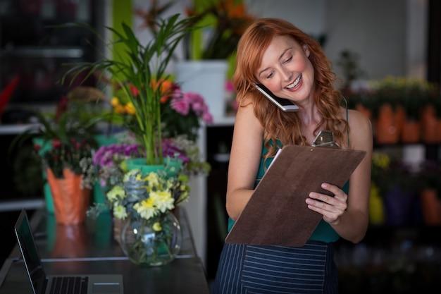 Fleuriste prenant la commande sur téléphone mobile