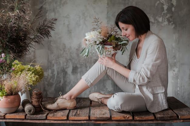 Fleuriste professionnel féminin prépare l'arrangement de fleurs sauvages.