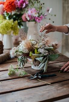 Fleuriste professionnel féminin prépare l'arrangement des fleurs sauvages.