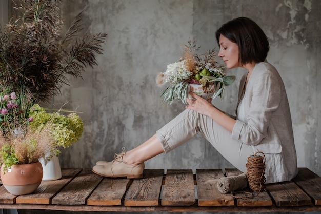 Fleuriste professionnel femme prépare l'arrangement de fleurs sauvages.
