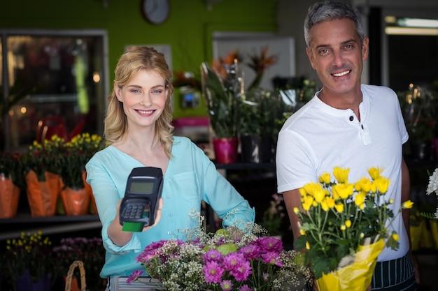Fleuriste souriant montrant le terminal de carte de crédit dans un magasin de fleurs