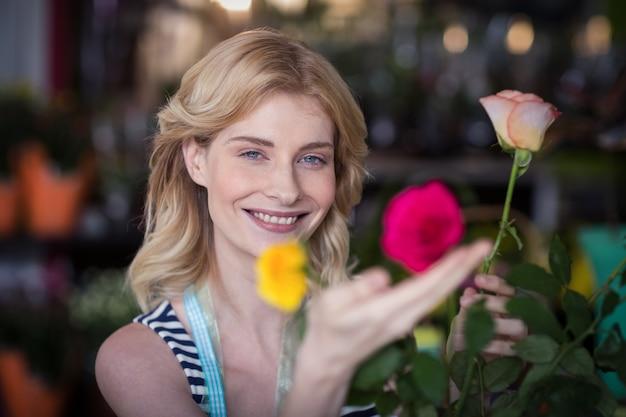 Fleuriste souriante organisant un bouquet de fleurs dans un vase au magasin de fleurs