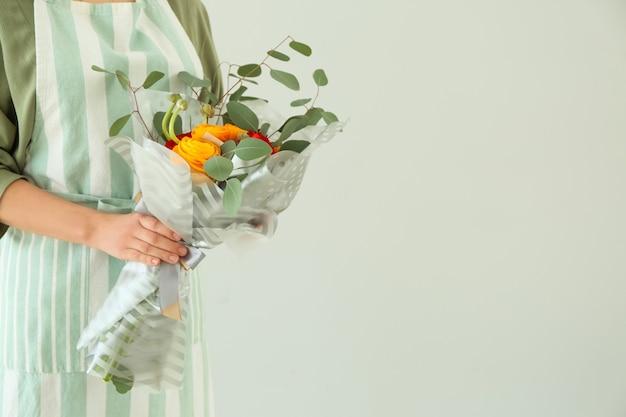 Fleuriste tenant un beau bouquet sur la lumière