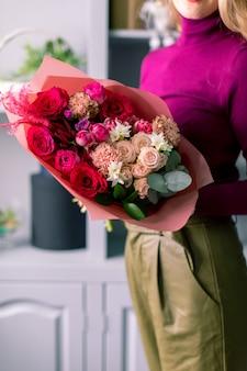 Fleuriste tenant un bouquet. belles fleurs de printemps. arrangement avec des fleurs mixtes.