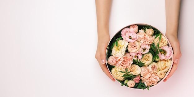 Fleuriste tenant un chapeau boîte ronde avec composition florale sur fond rose avec espace copie. coffret cadeau pour le 8 mars, saint valentin, fête des mères, anniversaire. mariage.