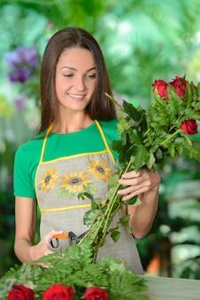 Fleuriste en train de préparer des bouquets de fleurs.