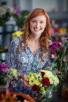 Fleuriste vérifiant un arrangement de fleurs dans un vase