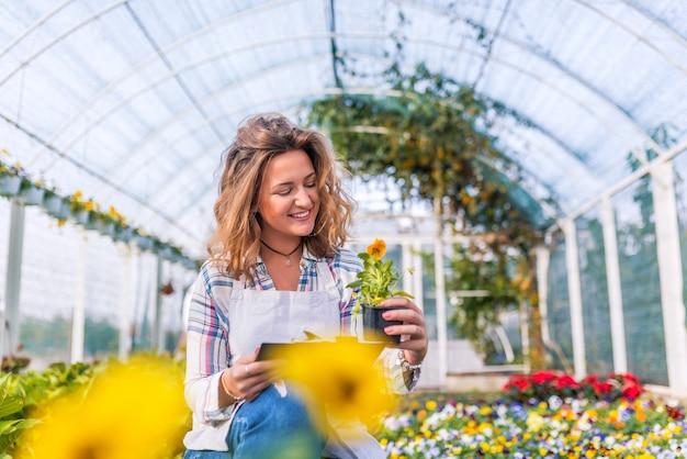 Fleuriste vérifiant l'état des fleurs en serre