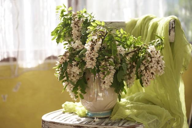 Fleurs d'acacia dans un vase blanc. nature morte avec fleurs d'acacia sur shair vintage.