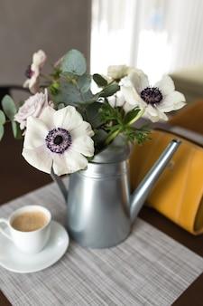 Fleurs d'anémones délicates dans un vase en métal avec une tasse de café sur la table en bois, sac à main jaune.