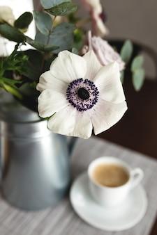 Fleurs d'anémones délicates dans un vase en métal avec une tasse de café sur la table en bois.