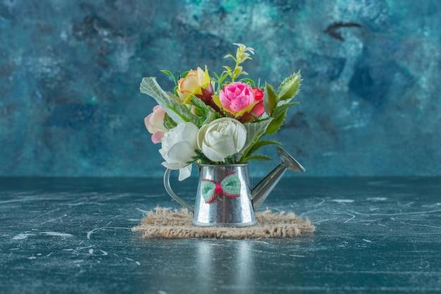 Fleurs artificielles dans un arrosoir, sur fond bleu.