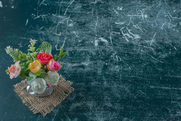 Fleurs Artificielles Dans Un Arrosoir, Sur Fond Bleu. Photo gratuit