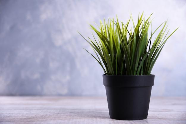 Fleurs artificielles herbe forme différente dans un pot sur fond en bois se bouchent avec copie espace et texte