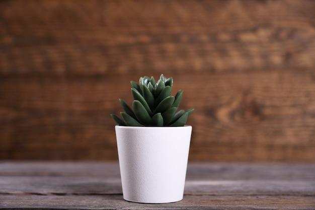 Fleurs artificielles herbe forme différente dans un pot sur fond de bois
