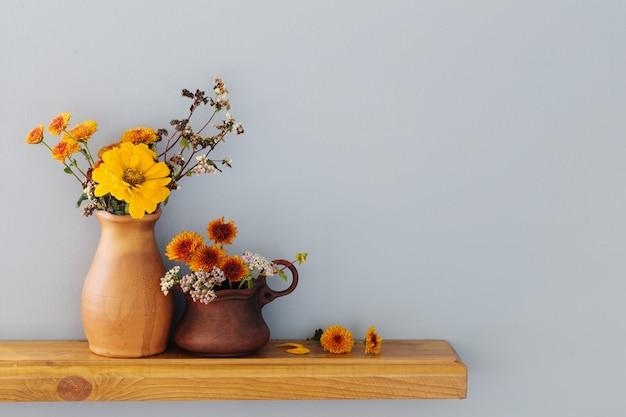 Fleurs d'automne dans un vase en céramique rustique sur fond gris mur