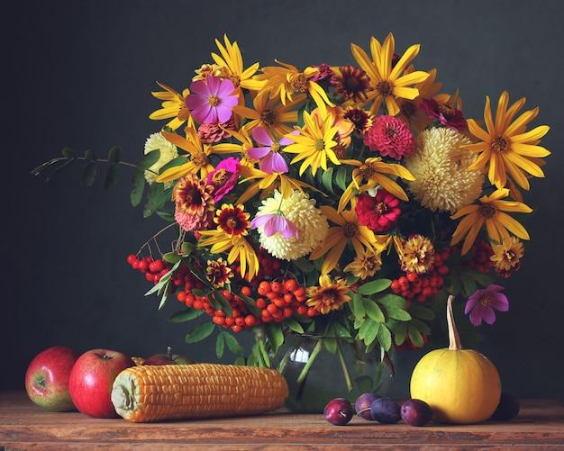 Fleurs d'automne en pot, fruits et légumes sur la table