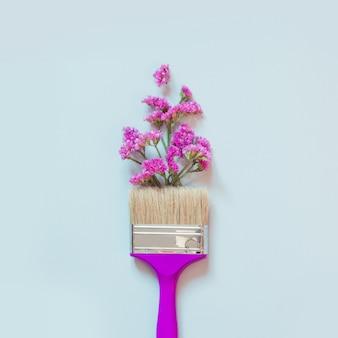 Fleurs d'automne violettes et roses et pinceau sur bleu.
