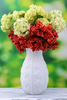 Fleurs et baies dans un vase, sur une table en bois, sur une surface lumineuse