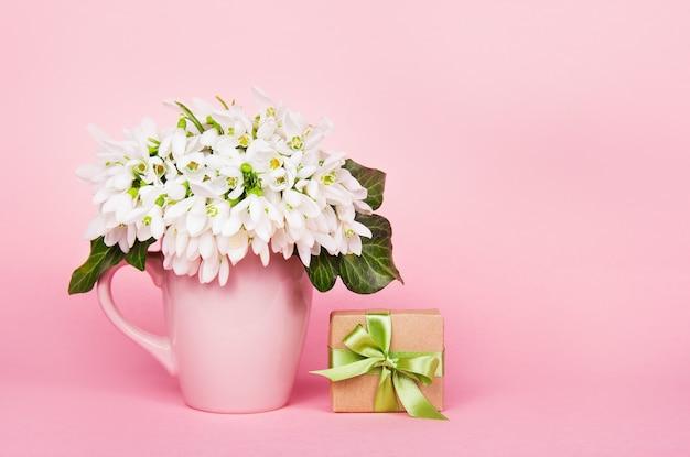 Fleurs blanches et coffret cadeau sur fond rose