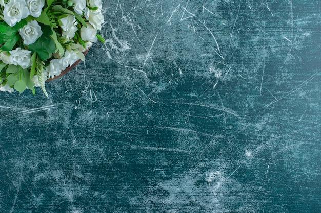 Fleurs blanches dans une assiette en bois, sur fond bleu.