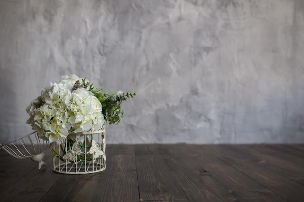 Des fleurs blanches dans une cage blanche se dressent sur un plancher en bois sur fond gris. bouquet de la mariée