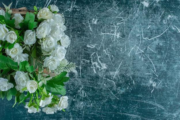 Fleurs blanches dans un porte-serviettes, sur fond bleu.