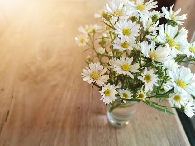 Fleurs blanches dans un pot en métal sur la table en bois