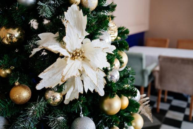 Fleurs blanches décoratives sur le sapin de noël. jouets originaux sur l'épicéa artificiel. nouvel an.