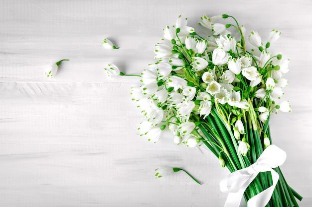 Des fleurs blanches de loddon lily reposent sur des planches en bois blanc.