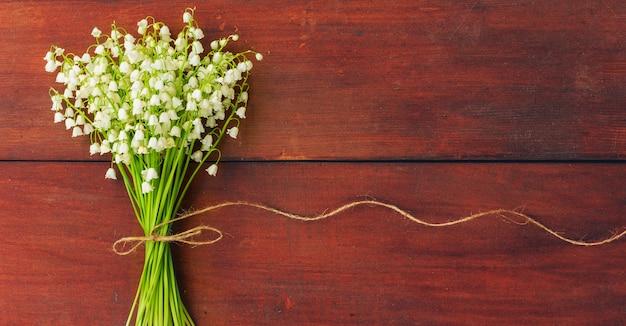 Fleurs blanches lys de la vallée sur des planches en bois brunes. fond espace libre pour le texte