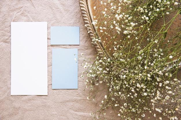 Fleurs blanches sur un plateau et des morceaux de papier