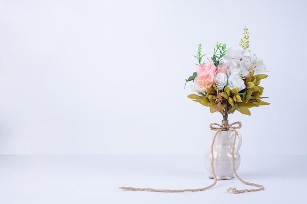 Fleurs blanches et roses dans un vase en céramique sur blanc.