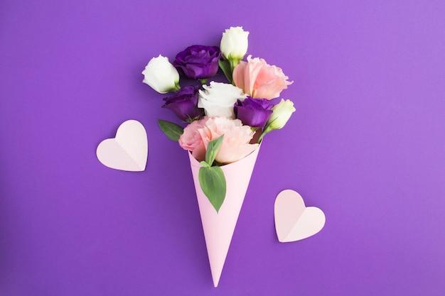 Fleurs blanches, roses et violettes dans un cône papier rose et coeurs roses sur fond violet